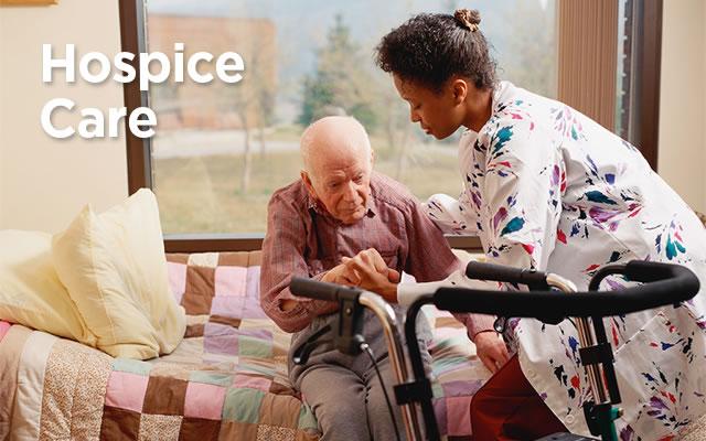 Nurse helping elderly man in hospice care